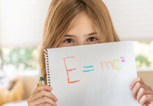 Girl (8-9) Holding Paper With Emc2 Formula In Front Of Face