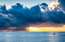 Dramatic Sunset Sky Over Sea With Silhouette Of Person Paddleboarding