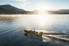 USA, New York, Lake Placid, Man In Motorboat On Lake Placid