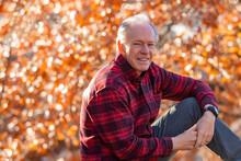 USA, Idaho, Boise, Outdoor Portrait Of Smiling Senior Man Sitting Outside In Autumn
