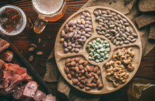 Salty Snacks With Nuts, Fried Corn, Chips, Smoked Meat, Sausage, Prosciutto, Cheese Sticks And Mugs With Beer On Wooden Background. Appetizers For Party, Beer Bar, Pub, Top View, Toning