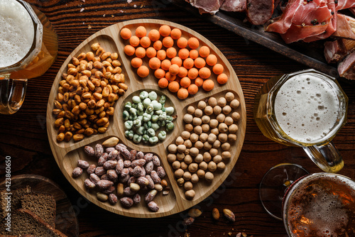 Fototapeta Salty snacks with nuts, fried corn, chips, smoked meat, sausage, prosciutto, cheese sticks and mugs with beer on wooden background. Appetizers for party, beer bar, pub, top view obraz