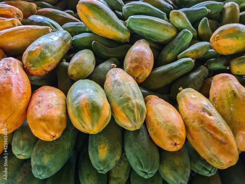Mamões maduros e verdes empilhados em um mercado de frutas