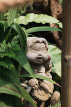 Happy Girl Doll Made From Stucco Decoration In A Garden