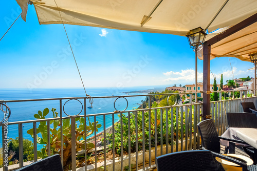 Fotografia View from a hillside cafe's covered patio seating of the Mediterranean sea and coastline of Taormina, Italy, on the island of Sicily
