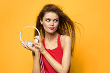 Cheerful Woman In Headphones Listens To Music In A Red T-shirt Yellow Background