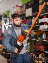 Portrait Of Yung Man With An Electric Brush Cutter In Hardware Store