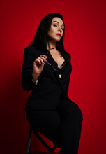 Gorgeous Adult Woman In Official Pantsuit With Deep Neckline Sits Sexy Posing With Glasses In Hand And Looking Down At Us Over Red Background. Fashion, Style, Trendy Business Look For Female Concept