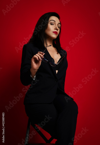 Fotografia, Obraz Gorgeous adult woman in official pantsuit with deep neckline sits sexy posing with glasses in hand and looking down at us over red background