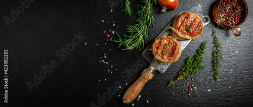 Fototapeta Premium Beef Steak. portion of juicy beef tenderloin steak covered bacon served on old meat butcher on dark concrete background with spices. Long banner format. top view obraz