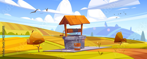 Obraz Old stone well with drinking water on yellow hill. Vector cartoon autumn landscape with fields, orange bushes and vintage well with wooden roof, pulley and bucket - fototapety do salonu