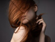 Red hair silk model gray background naked shoulders passionate look