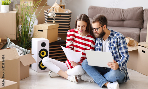 Obraz Cheerful couple with laptop discussing insurance of new home - fototapety do salonu