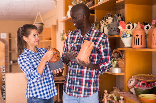 Foto Loving happy couple choosing stoneware in pottery store