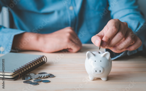 Wallpaper Mural close up businessman holding coins putting in piggy bank the book and coins in front