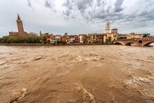 The River Adige In Flood In Verona Downtown After Several Violent Storms. Church Of Santa Anastasia, Ponte Pietra, Bell Tower Of The Cathedral And The Lamberti Tower. Veneto, Italy, Europe.