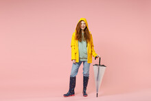 Full Length Redhead Young Woman In Yellow Waterproof Raincoat Hood Outerwear Hold Folded Transparent Umbrella Isolated On Pink Background Studio. Outdoors Lifestyle Wet Fall Weather Season Concept