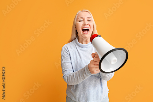 Fotografie, Obraz Stressed mature woman with megaphone on color background