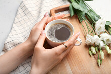 Female Hands With Cup Of Coffee And Spring Flowers On Light Background