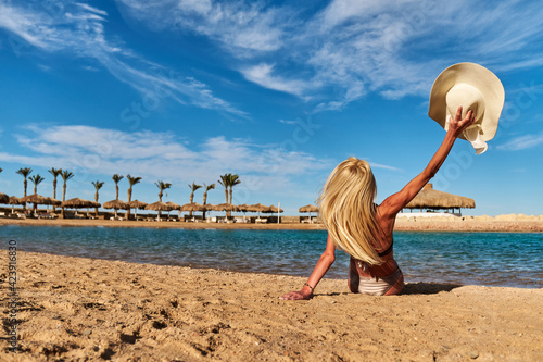 Canvas Print Young fashion woman sitting on the beach shore