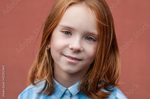 Portrait of a red-haired child with green eyes 8 years old in a blue shirt on a teracot background Fototapeta
