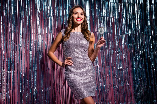 Fototapeta Portrait of attractive cheerful girl drinking wine retro fest 80s prom theme evening isolated on glossy tinsel colorful background obraz na płótnie