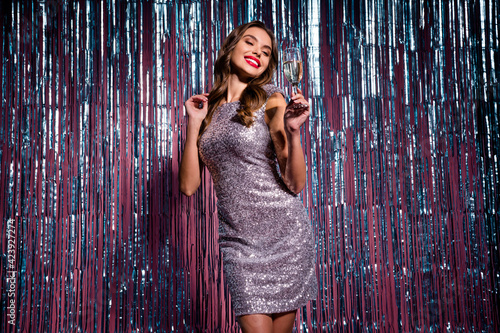 Fototapeta Photo of young attractive charming smiling classy girl enjoying party drinking champagne isolated on glittered background obraz na płótnie
