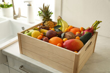 Wooden Crate With Assortment Of Exotic Fruits On Table In Kitchen