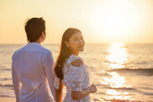 Young Happy Asian Couple Holds Hands On The Beach With A Woman Facing Camera Drum, Romantic Travel Honeymoon Summer Holidays. Asian Woman And Man Holding Hands Embracing Outdoors On Sunset Background