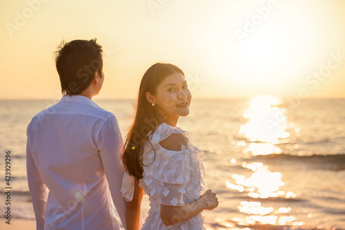 Canvas Print Young happy Asian couple holds hands on the beach with a woman facing camera drum, romantic travel honeymoon summer holidays