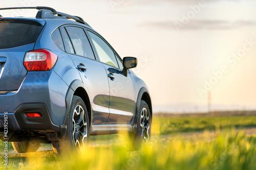Obraz na plátně Landscape with blue off road car on gravel road
