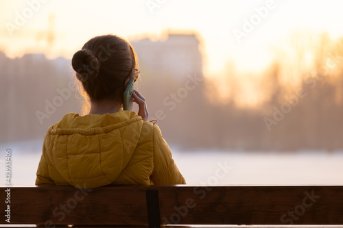 Young pretty woman sitting on a bench talking on her mobile phone outdoors in the evening.