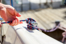 Human Hand On Sailing Boat Or Yacht Tying A Knot, Close Up View