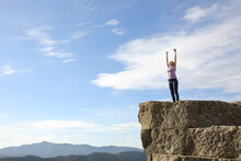 Excited Runner Raising Arms In The Top Of A Cliff