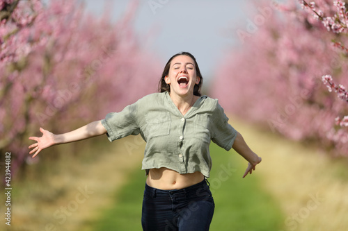 Obraz Happy woman running celebrating vacation in a field - fototapety do salonu