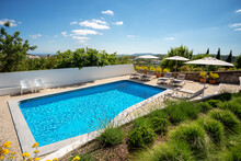 Outdoors Shot Of A Clean Pool With Some Loungers On The Side On A Clear Sunny Day.