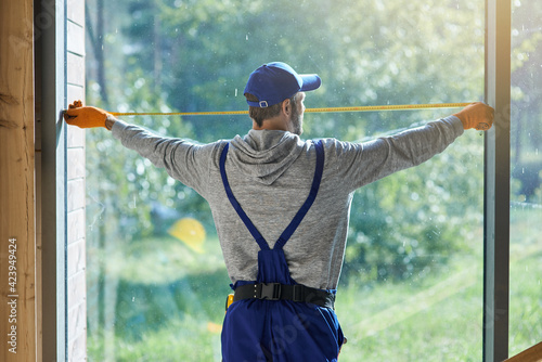 Obraz na plátně Rear view of young workman wearing blue overalls using measuring tape while work