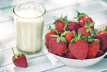 Ripe Strawberries And A Glass Of Homemade Milk On A Light Wooden Background. Selective Focus With Shallow Depth Of Field.