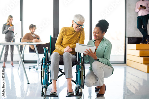Obraz Senior business woman in wheelchair working in office - fototapety do salonu