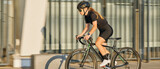 Website header of Side view of professional female cyclist in black cycling garment and protective gear riding bicycle in city, rushing and passing outdoors on a sunny day
