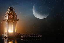 Muslim Lamp And Tasbih On Table Against Night Sky