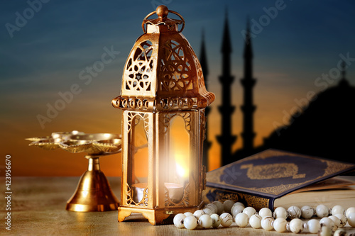 Muslim lamp, tasbih and Koran on table at sunset