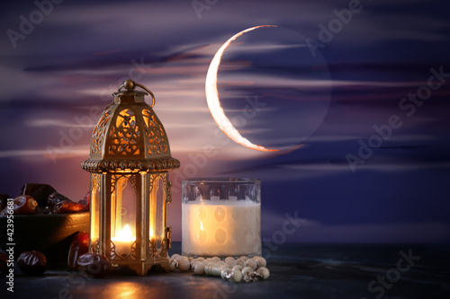 Obraz Muslim lamp, glass of milk and tasbih with dates on table against night sky - fototapety do salonu