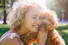 Adorable Maltipoo Puppy In Arms Of Its Loving Owner. Adult Woman Outdoors Playing With Her Small Adorable Doggy In The Park. A Hybrid Between The Maltese Dog And Miniature Poodle. Close Up, Copy Space