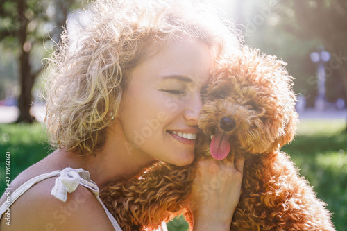 Obraz Adorable maltipoo puppy in arms of its loving owner. Adult woman outdoors playing with her small adorable doggy in the park. A hybrid between the maltese dog and miniature poodle. Close up, copy space - fototapety do salonu
