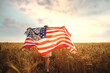 Back view of a girl in white dress wearing an American flag while running in a beautiful wheat field