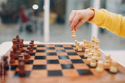 Fotografie, Obraz Little kids playing chess at kindergarten or elementary school