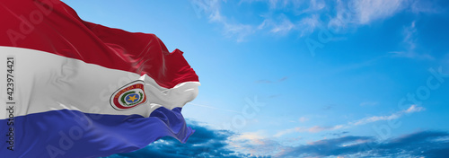 Photo Large flag of Paraguay  waving in the wind on flagpole against the sky with clouds on sunny day