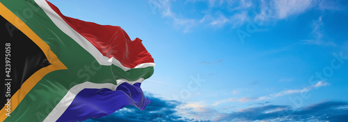 Fotografie, Obraz Large flag of South Africa  waving in the wind on flagpole against the sky with clouds on sunny day