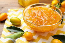 Delicious Kumquat Jam In Bowl And Fresh Fruits On Table, Space For Text